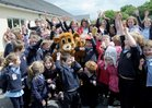 Children celebrate with a bear at a party  after the raising of the Green Flag at Tuairin' National School, Moycullen.
