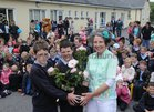 Pupils Cathail Mac Sea'n and Danial O Feinne make a presentation of flowers to Anne Carroll, Green Flag co-ordinator  after the raising of the Green Flag at Tuairin' National School. <br />