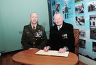 <br /> Lt Col (Retired) Ned Cusack Moycullen signs the distinguished Visitors book at his hundred Birthday celebrations at Dun UI Mhaoiliosa, Renmore with Lt Col Frank Flannery, OC 1CnCois.