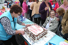Margaret Murphy gives a hand at cutting Eileen's birthday cake
