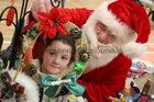 Santa Claus shows some Christmas gifts to Tulisa Kavanagh (6) from Bohermore at the Ballybane Christmas Fair in the Ballybane Community Centre last Saturday.