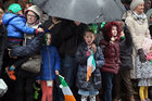 Children take shelter during the heavy rain at the St Patrick's Day Parade in the city.