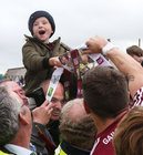 A young supporter gets to hold the J J Nestor Cup as Galway players celebrate after defeating Roscommon to win the Connacht Senior Football final at Dr Hyde Park in Roscommon.