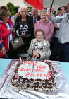 Eileen Molloy cutting her 100th birthday cake at the surprise party in Davis Road.