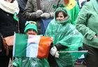 Keeping covered during the heavy rainfall at the St Patricks Day Parade in the city centre.