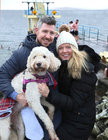 Tomás and Michelle Treacy from Claregalway with their goldendoodle Bonnie at Blackrock to watch the swimmers on Christmas Day.