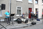 Jackie Kelly, P J Duggan and Paul Grealish sing and play music to lighten the spirits of neighbours and friends at St Brigit's Terrace, Prospect Hill,