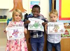 Ellie, Samuel and Christopher display their colouring work during their first day at school in St Nicholas' Parochial School, Waterside.